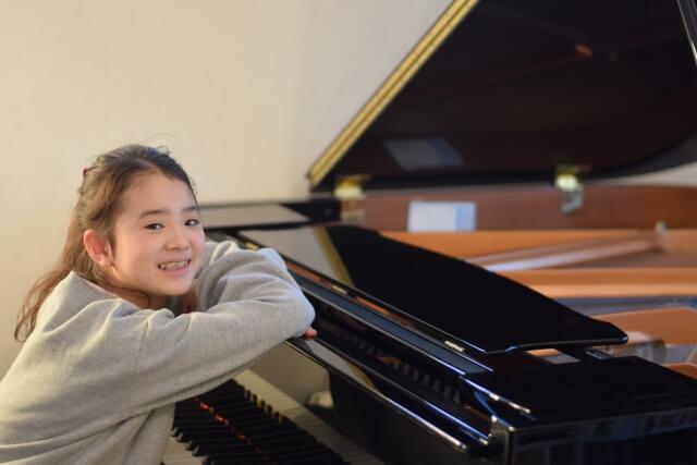 ピアノにもたれる少女