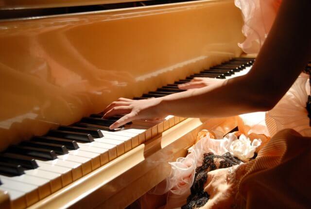 ピアノを弾くドレスの女性の両手